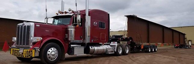 Red truck hauling a large I beam