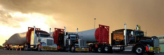2 trucks at sunset with heavy loads